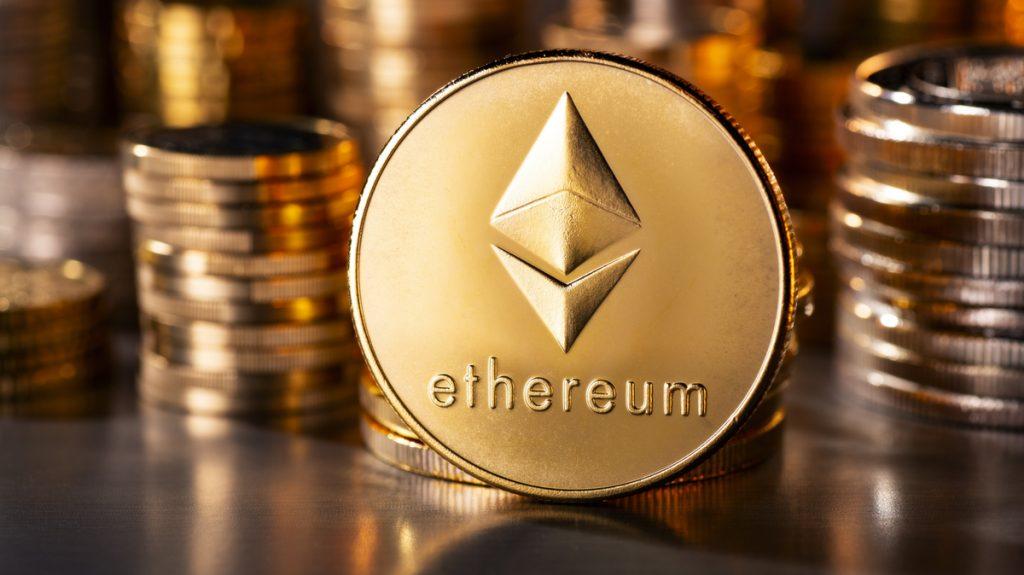 Imagen de una moneda de Etherum de color dorado, con pilas de monedas desenfocadas al fondo